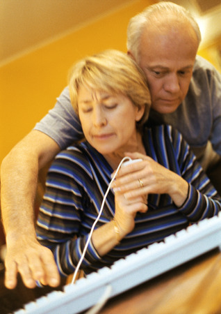 Mature couple, man pressing key on keyboard, woman holding computer mouse