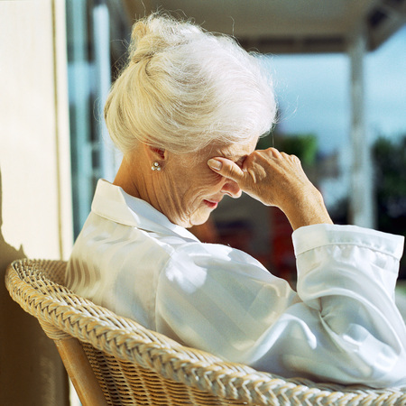 Senior woman sitting in sun with hand over eyes, side view