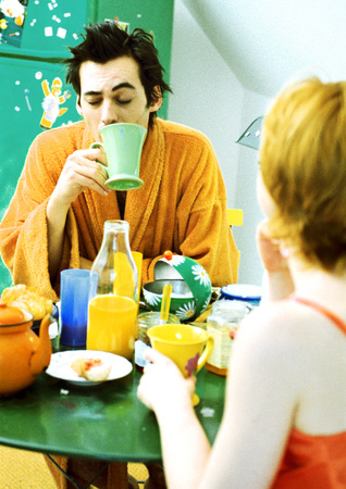 Young couple sitting at table having breakfast, woman in rear view