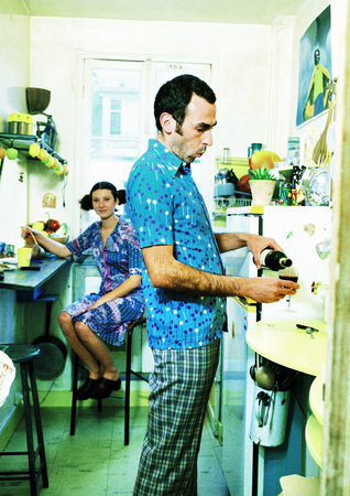inebriated: Couple in kitchen, woman sitting, man pouring wine