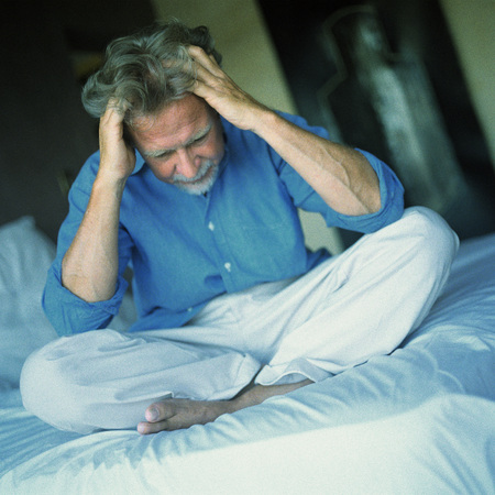 unease: Man sitting indian style on bed, both hands in hair LANG_EVOIMAGES