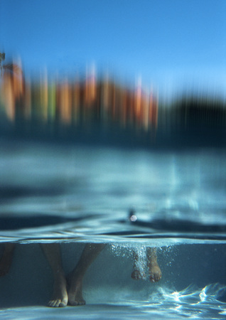Two pairs of feet in water, underwater view