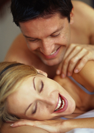 adultery: Couple lying on bed, smiling