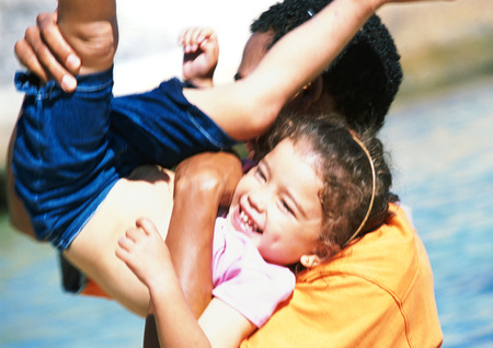 multi racial: Man holding daughter on his shoulder with legs in the air, girl laughing LANG_EVOIMAGES