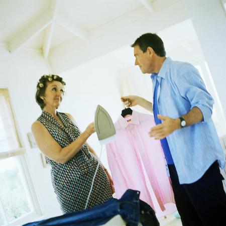 Mature couple facing each other, man holding shirt, woman handing him iron