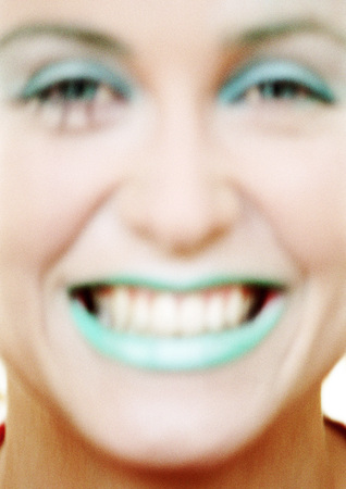Woman with green lipstick smiling, close-up LANG_EVOIMAGES
