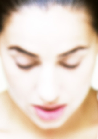 Woman looking down, close-up, blurred LANG_EVOIMAGES