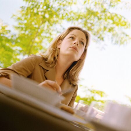 distractions: Woman sitting at table outside, low angle view LANG_EVOIMAGES