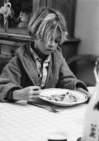 Child sitting with plate, portrait, b&w LANG_EVOIMAGES