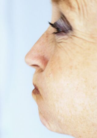 Mature woman puffing out cheeks, close-up, side view LANG_EVOIMAGES