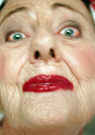 trashy: Senior woman wearing red lipstick looking at camera, portrait, extreme close-up