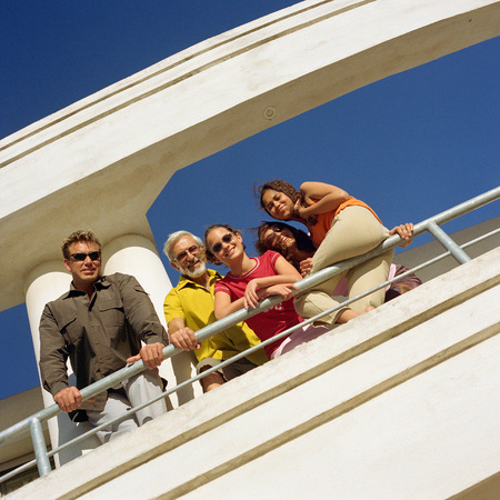 Family leaning on railing, low angle view