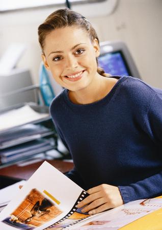 Woman sitting at desk, smiling, portrait LANG_EVOIMAGES