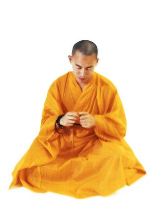 Buddhist monk sitting and meditating, holding prayer beads