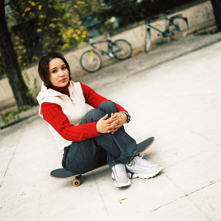 Young woman sitting on skateboard, portrait