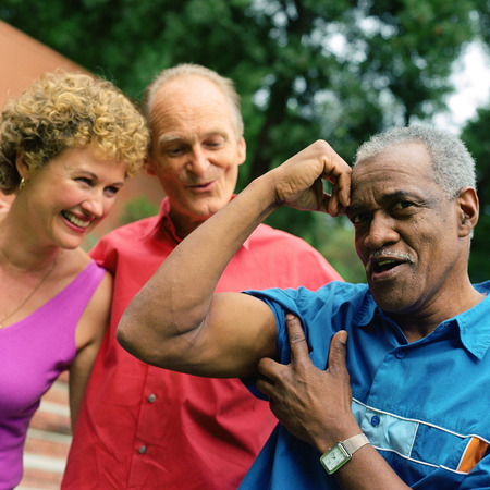 brincando: Three people standing outside, man flexing arm muscles