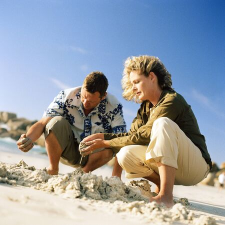 Couple digging in sand