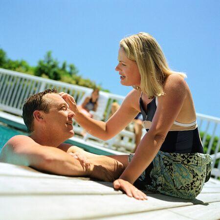 Loving couple at resort, man talking to woman sitting on edge of pool