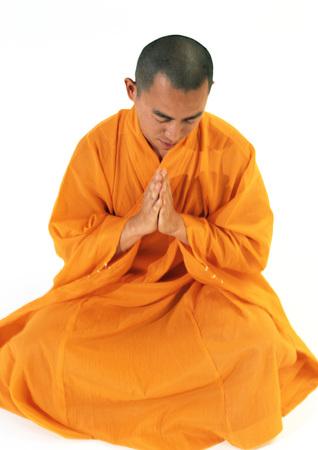 Buddhistischer Mönch sitzt, meditiert mit den Händen zusammen, High Angle View