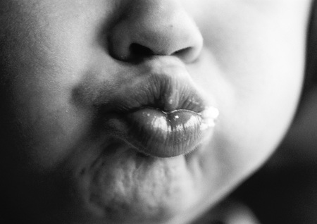 puckered lips: Child puckering lips, close-up on mouth, b&w