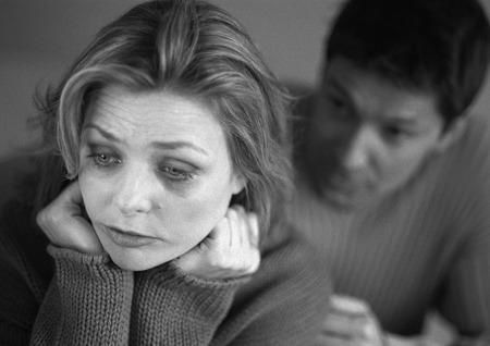 Man standing behind tearful woman, close-up, b&w LANG_EVOIMAGES