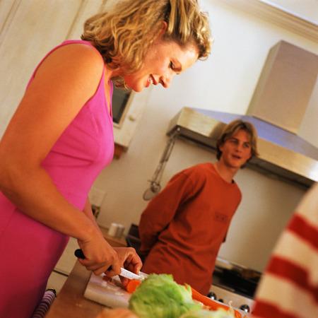 range hood: Mother preparing food in kitchen, teenage son in background