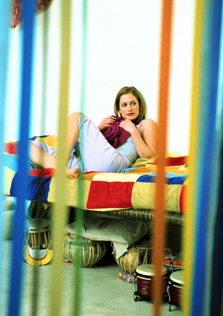 Young woman sitting on bed LANG_EVOIMAGES