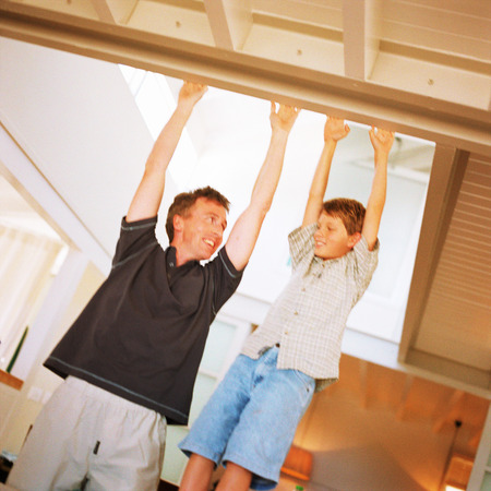 Father and son reaching to touch ceiling beam, smiling