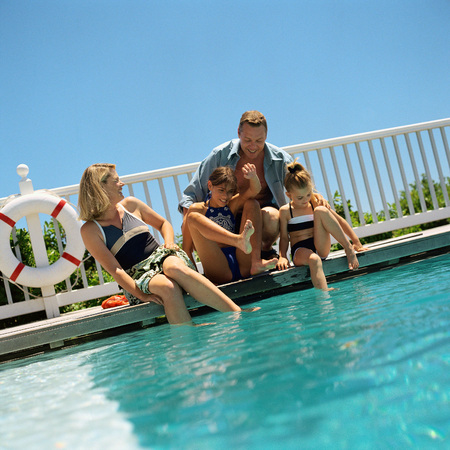 Family sitting at edge of swimming pool
