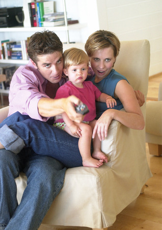 Couple holding baby, sitting on chair, pointing remote control