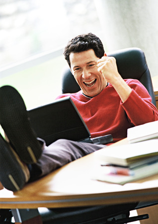 Man with laptop on lap and feet on desk, smiling LANG_EVOIMAGES