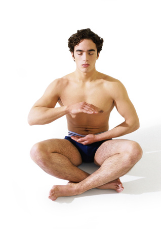 Man in underwear sitting indian style on floor with hands hovering in front of torso