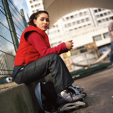 chainlink fence: Young woman wearing inline skates, portrait