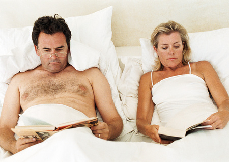 Couple lying in bed, reading