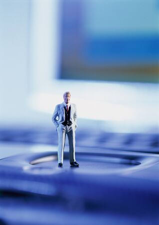 Small toy figure standing on computer keyboard, focus on figure
