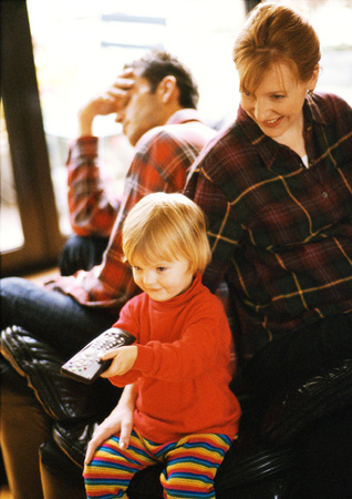 Child sitting in front of parents, pointing remote control