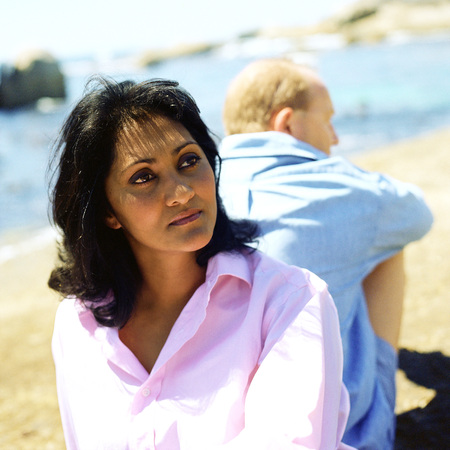 Couple sitting back to back on beach, focus on woman