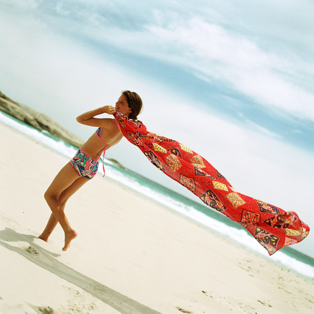 Girl in swimsuit on beach holding sarong in wind LANG_EVOIMAGES