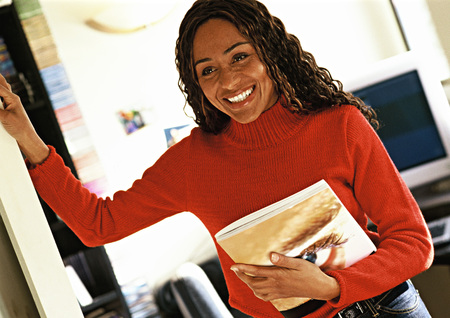 Woman holding catalog in office, smiling