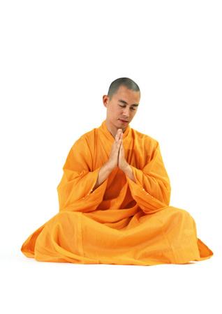 Buddhistischer Mönch sitzt, meditiert mit den Händen zusammen, Vorderansicht