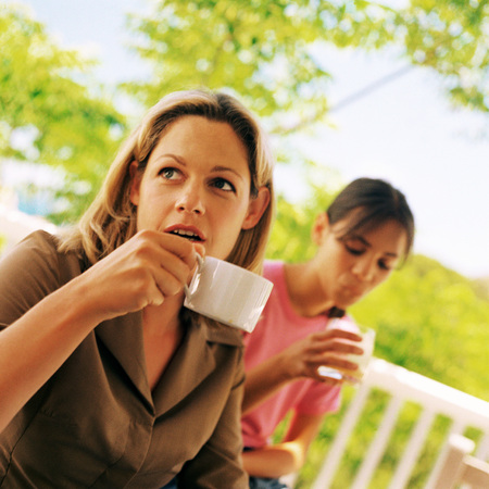 Woman holding teacup, girl holding glass LANG_EVOIMAGES