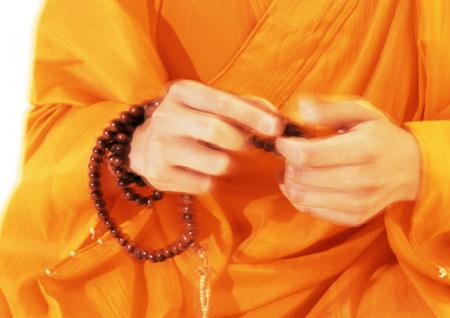 Buddhist monks hands holding prayer beads