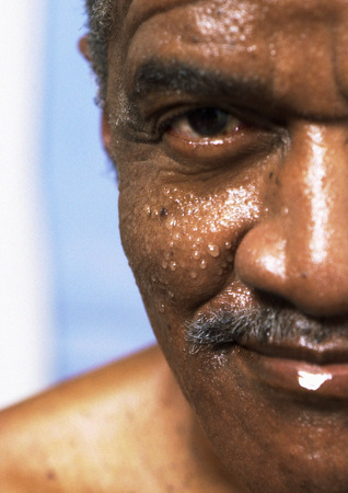 Senior man with wet face looking into camera, close-up of one side of face