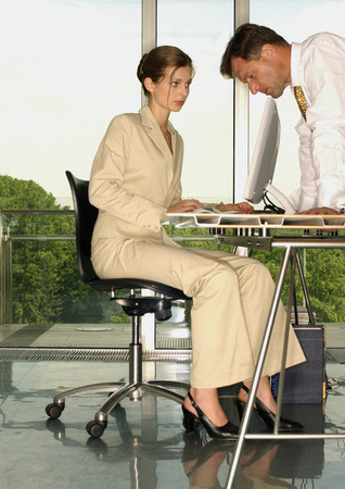 Businessman and woman looking at screen LANG_EVOIMAGES