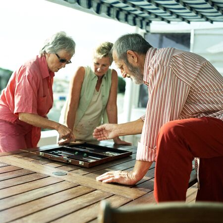 Three mature friends playing backgammon LANG_EVOIMAGES