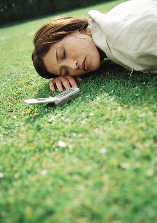 Woman lying on grass with cell phone near head, close-up