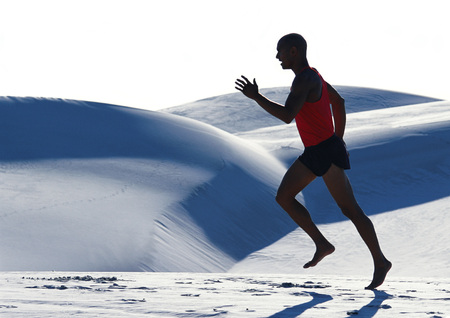 overcoming adversity: Barefooted man, running across dune, side view LANG_EVOIMAGES