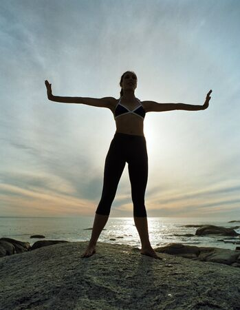 Woman standing on beach, arms extended out, silhouette LANG_EVOIMAGES