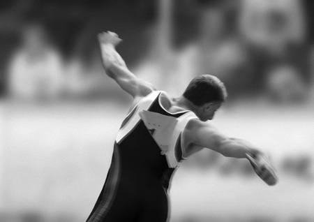 lanzamiento de disco: Male athlete throwing discus, rear view, b&w LANG_EVOIMAGES