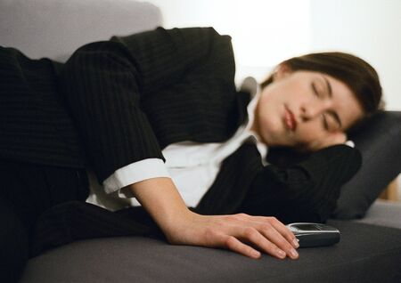 burned out: Businesswoman lying on couch, eyes closed, hand on cell phone LANG_EVOIMAGES